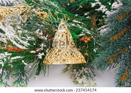 Christmas bells and fir-tree branch on gray background. - stock photo