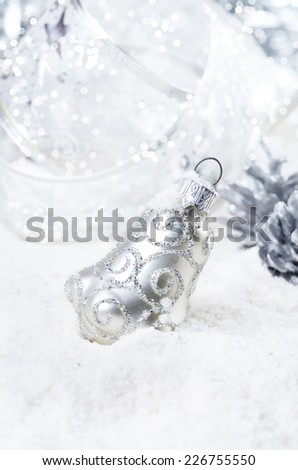 Christmas bells baubles on snow over bright background - stock photo