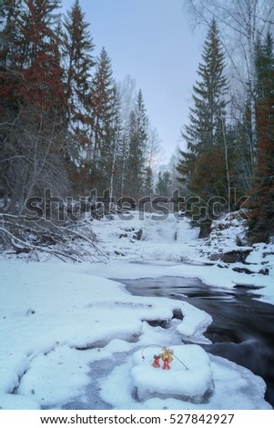 christmas bells, trees and icicles of river with snow  and rocks