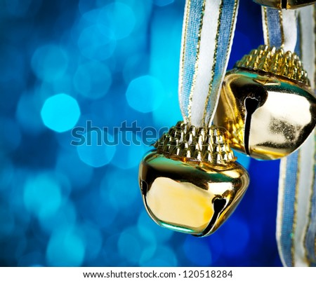 Christmas bells with ribbon,  defocused blue lights on  background - stock photo
