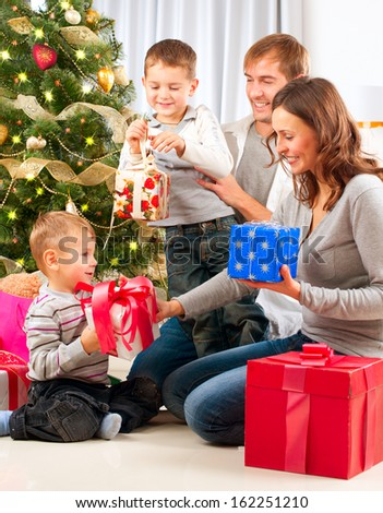 Christmas Big Family with Children near the Christmas Tree at home. Happy Children Opening Gift.   - stock photo