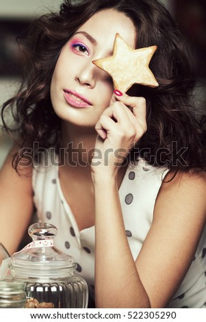 Christmas biscuit concept. Portrait of young brunette with arty make-up hiding her eye with gingerbread, posing with glass container full of cookies in cafe, restaurant. Retro style. Indoor shot