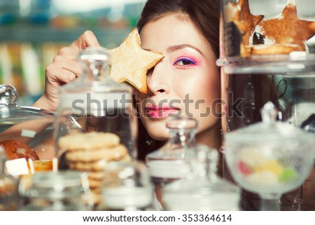 Christmas biscuit concept. Portrait of young brunette with arty make-up holding gingerbread posing with glass containers full of cookies in vintage cafe, restaurant. Retro style. Close up. Indoor shot