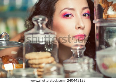 Christmas biscuit concept. Portrait of young brunette with arty make-up posing over glass containers full of cookies , gingerbread in vintage cafe, restaurant. Retro style. Close up. Indoor shot - stock photo
