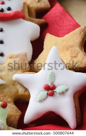 Christmas biscuits (cookies) in various shapes, decorated with icing (frosting).  Star shape in foreground.