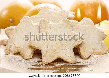 Christmas biscuits in star shape. Fresh oranges and candles around. Christmas mood. - stock photo