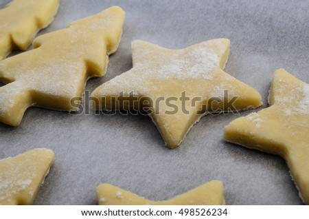 Christmas biscuits or cookie shapes, cut from raw pastry dough on baking parchment paper, ready to go into oven.