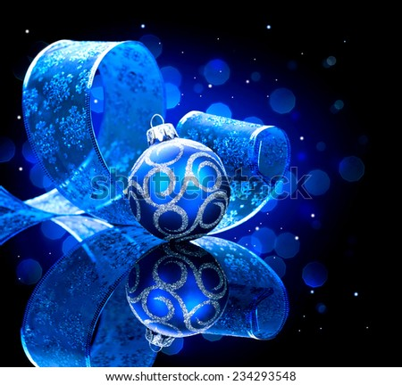 Christmas blue baubles with ribbon and stars over black background. New Year decoration art design - stock photo
