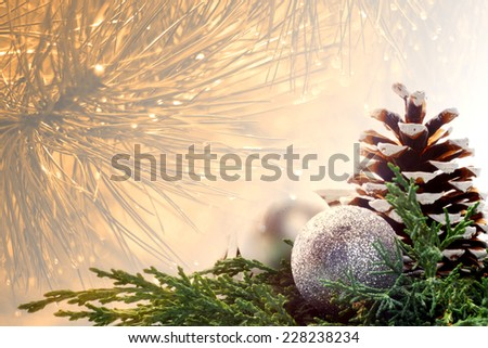 Christmas blurred background - gold pine needles with drops of water with christmas decoration - pinecone and pair of balls - ornaments on green pine needles