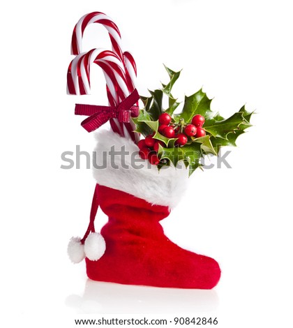 christmas boot stocking  filled  gifts ,sprig Christmas tree holly and  lollipop stick  isolated  on white background - stock photo