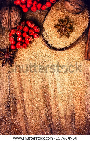 Christmas border design background with winter spices anise star, cinnamon sticks, cane brown sugar and winter berries. Vintage old wooden background. - stock photo