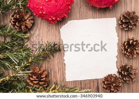 Christmas border design with pine cone, fir branches and christmas balls on parchment paper over old oak wood