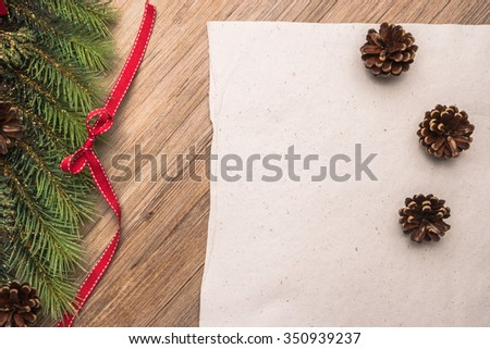 Christmas border design with pine cone, fir branches and ribbon on parchment paper over old oak wood