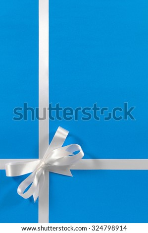 Christmas border gift ribbon bow, blue wrapping paper background, vertical - stock photo