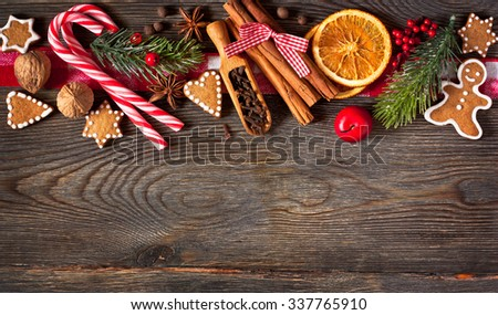 Christmas border. Gingerbread cookies, spices and decorations on wooden background. - stock photo
