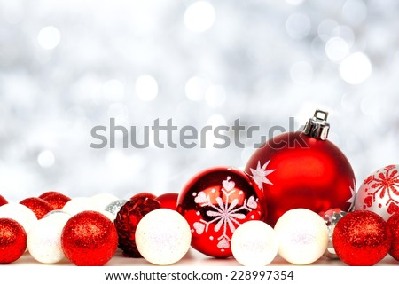 Christmas border of red and white ornaments over a twinkling silver light background