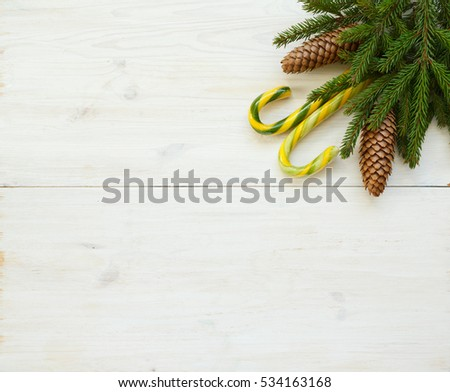 Christmas border with fir tree branches with cones and candy cane on white wooden boards ready for your design