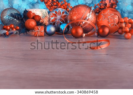Christmas border with orange and blue baubles and berries on wood. Shallow DOF, focus on the red bal with Star pattern. Space for your text. This picture is toned - stock photo