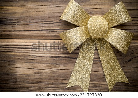 Christmas bow golden color. On colored paper background. - stock photo