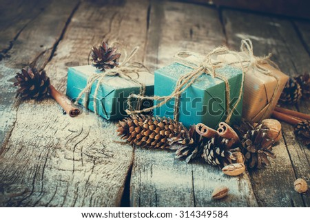 Christmas Boxes with Linen Cord, Cinnamon, Pine cones, Nuts. Natural Decor on Wooden Background. Toned - stock photo
