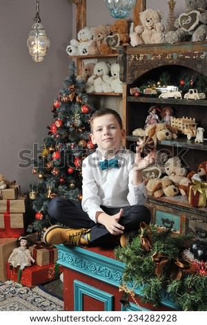 Christmas boy and the Nutcracker around Christmas tree with gifts