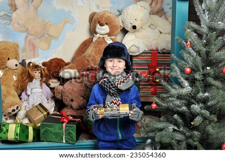 Christmas boy around the Christmas tree with gifts and toys Teddy bears - stock photo