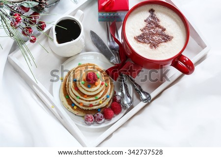 Christmas breakfast served on white tray with pancakes and cappuccino - stock photo