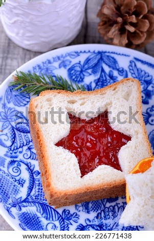 Christmas breakfast - slices of wholewheat toast with red cranberry marmalade spread in the shape of tree. - stock photo