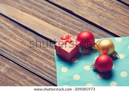 Christmas bubbles and gift box on wooden table.