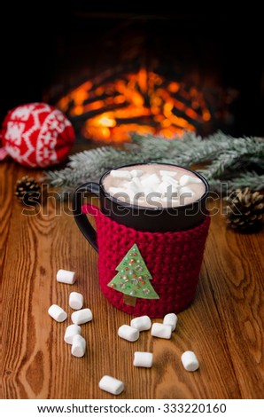 Christmas cacao in front of warm fireplace.Christmas tree and fir-cones. Holiday Christmas concept. Mug in red knitted mitten standing near fireside.Cozy relaxed magical atmosphere. - stock photo