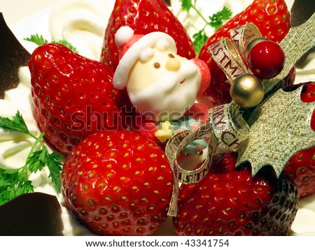Christmas cake decorated with Santa Claus candy and strawberries