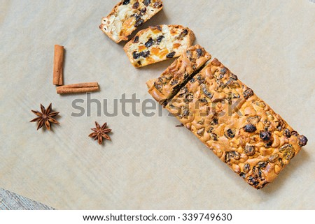 Christmas cake with cinnamon and anice on the baking paper, top view - stock photo