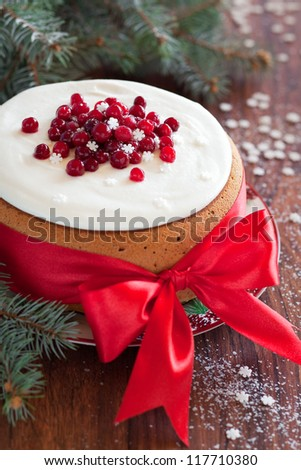 Christmas cake with cranberries, pistachios and cream cheese frosting. Selective focus - stock photo