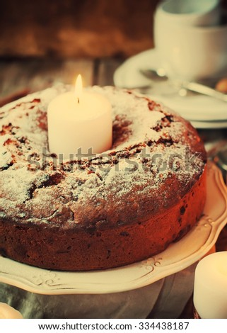 Christmas Cake with Powered Sugar on Vintage Plate. Festive Decoration Candle in the Middle on Wooden Table. Toned