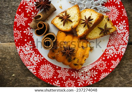 Christmas cake with spices, cinnamon and anise star,on th ered snowflake ornament plate