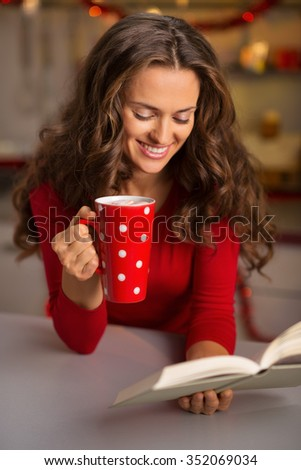 Christmas can be a stressful holiday. Don't forget to give yourself time on favourite things. Happy young woman having a cup of hot chocolate with marshmallows and reading a book - stock photo