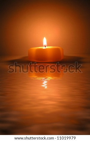 christmas candle and reflection in water