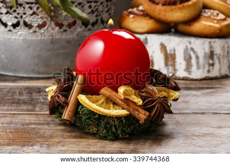 Christmas candle holder made of moss, dried fruits and cinnamon sticks - stock photo