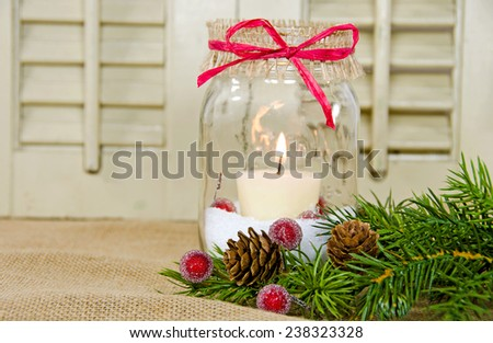 Christmas candle in a mason jar with pine bough and sparkling red berry - stock photo