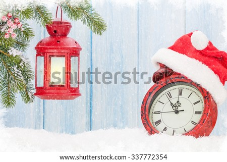 Christmas candle lantern and alarm clock with santa hat - stock photo