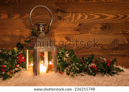 Christmas candle lantern in snow surrounded by holly with red berries against a rustic wooden background. - stock photo