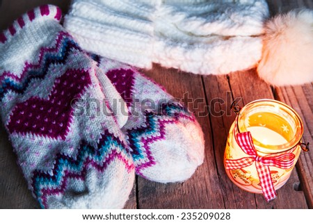 Christmas candle on vintage wooden background. Snowman on snow. Festive decorations. Classic gloves with cap - stock photo