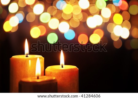 Christmas candle with blurred light on dark background