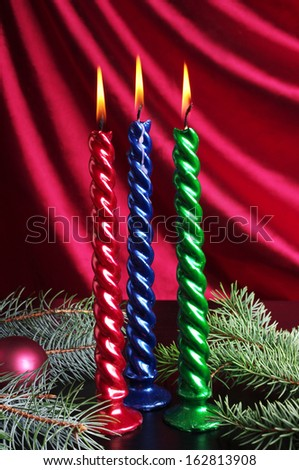 Christmas candle with decoration against purple drapery - stock photo