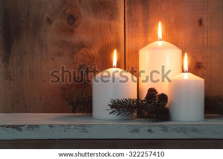 Christmas candles and fir branches over wooden background  - stock photo