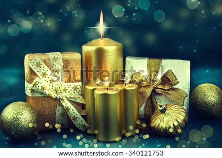 Christmas candles and ornaments over dark blue  background with lights
