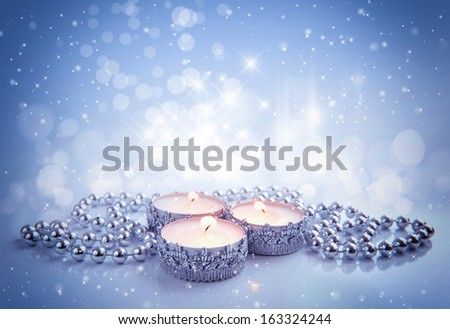 Christmas candles are with beads on a festive background - stock photo