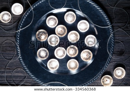 Christmas candles on a silver plate on an old wooden board, top view.