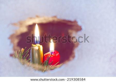 Christmas candles on a snowy window concept - stock photo
