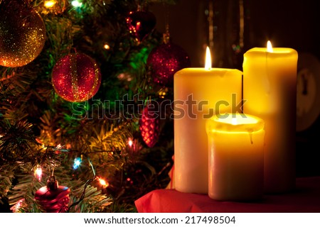 Christmas candles on fir tree lights background - stock photo